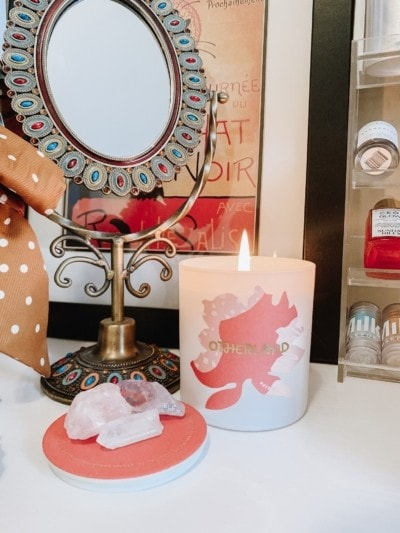 Otherland Daybed candle on a vanity with an antique mirror. Surround the candle is an antique mirror, a shelf of skincare products, and several quartz and amethyst crystals from Sunday Forever. Aromatherapy is a great way to relax and practice self-care.