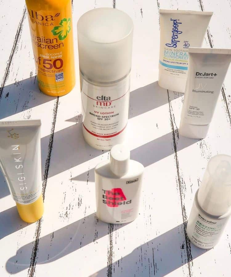 Several mineral and chemical sunscreen bottles standing on a white background. Elta MD sunscree, Supergoop mineral sunscree, KraveBeauty The Beet Shield and Beet the Sun, Sigiskin sunscreen, DR Jart sunscreen, mineral sunscreen and chemical sunscreen, SPF moisturizer